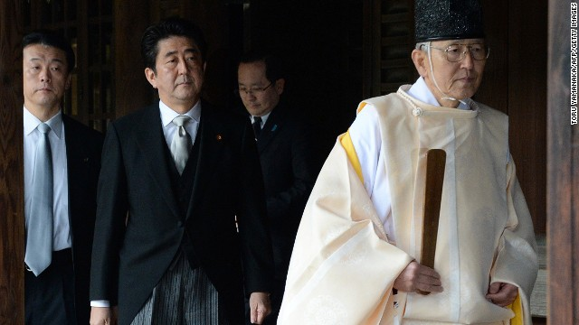 A Shinto priest (R) leads Japanese Prime Minister Shinzo Abe (C) as he visits the controversial Yasukuni war shrine in Tokyo on December 26, 2013, in a move Beijing condemned as 'absolutely unacceptable'. Abe described his visit, which is certain to roil already-troubled ties in East Asia, as a pledge against war and said it was not aimed at hurting feelings in China or South Korea. AFP PHOTO/Toru YAMANAKA (Photo credit should read TORU YAMANAKA/AFP/Getty Images)
