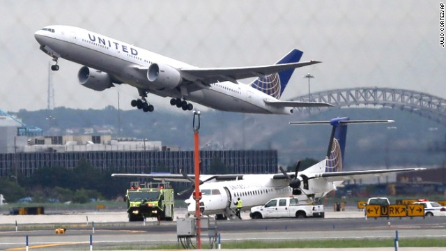 A United plane, top, takes off from Newark Liberty International Airport as officials investigate a passenger plane that landed safely after taking off from the airport after reporting smoke in the cockpit, Thursday, July 25, 2013, in Newark, N.J. Port Authority of New York and New Jersey spokesman Steve Coleman said United Express Flight 4890 was headed for Pittsburgh. The plane returned, stopped on the runway and 27 passengers were evacuated safely as a precaution. Coleman said no one was injured.