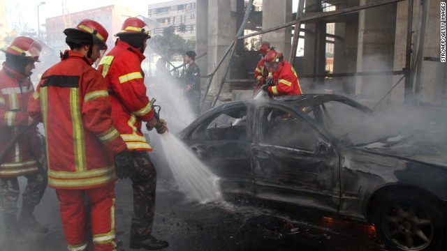 Firemen douse a burning car following a huge blast that rocked central Beirut on December 27, 2013