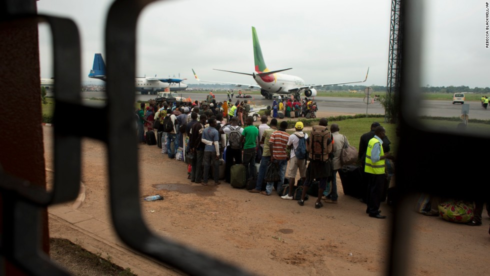 Cameroonians wait in line to board an evacuation flight at M'Poko International Airport, which is guarded by French soldiers on December 27. Military escorts shuttled citizens of Chad and Cameroon to the airport Friday to board evacuation flights as French troops stepped in to help Muslims fleeing north by road.