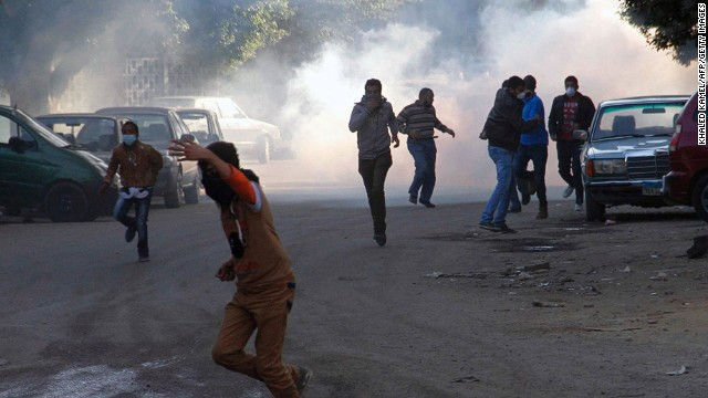 This file photo shows Muslim brotherhood supporters running for cover during clashes with police on the outskirts of Cairo on December 27, 2013.