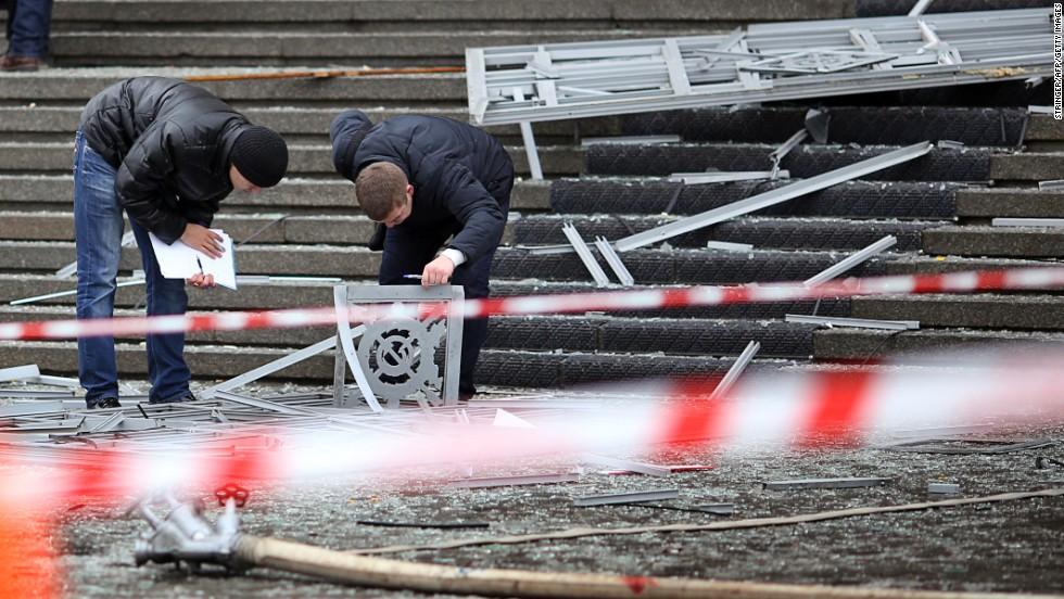 Police investigators inspect debris at the scene of the explosion.