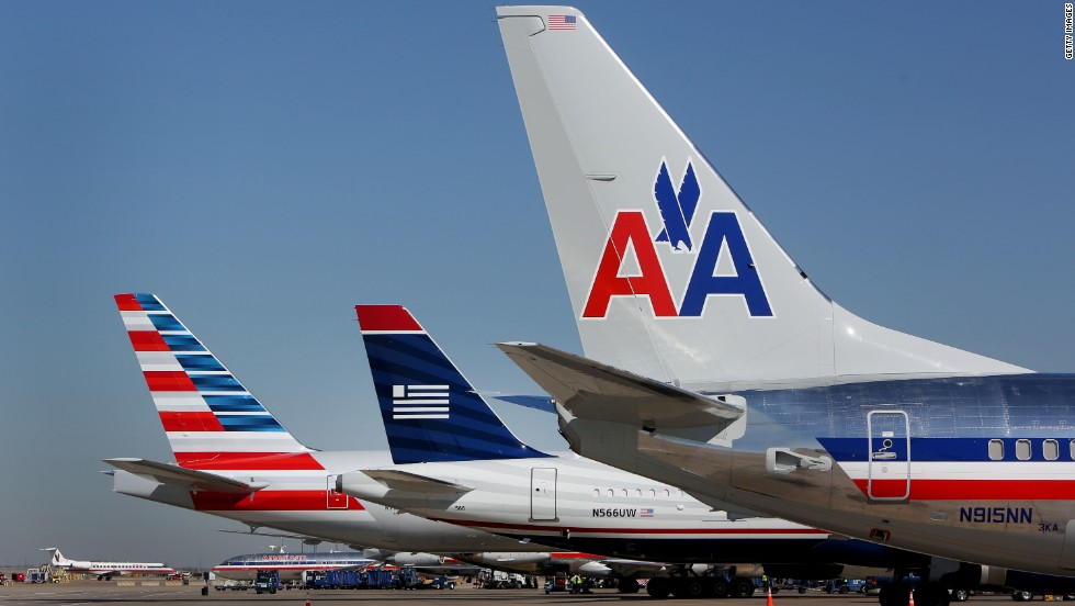 A US Airways airplane, center, is flanked by American Airlines jets at Dallas/Fort Worth International Airport on February 14, 2013. The two airlines merged in December 2013 to create the world's largest airline.