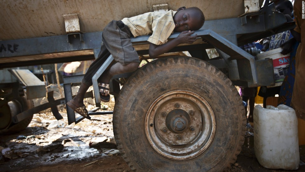 A boy rests on the fender of a water truck Tuesday, December 31, at a United Nations compound on the outskirts of Juba, South Sudan. The compound has become home to thousands fleeing the recent fighting in South Sudan.