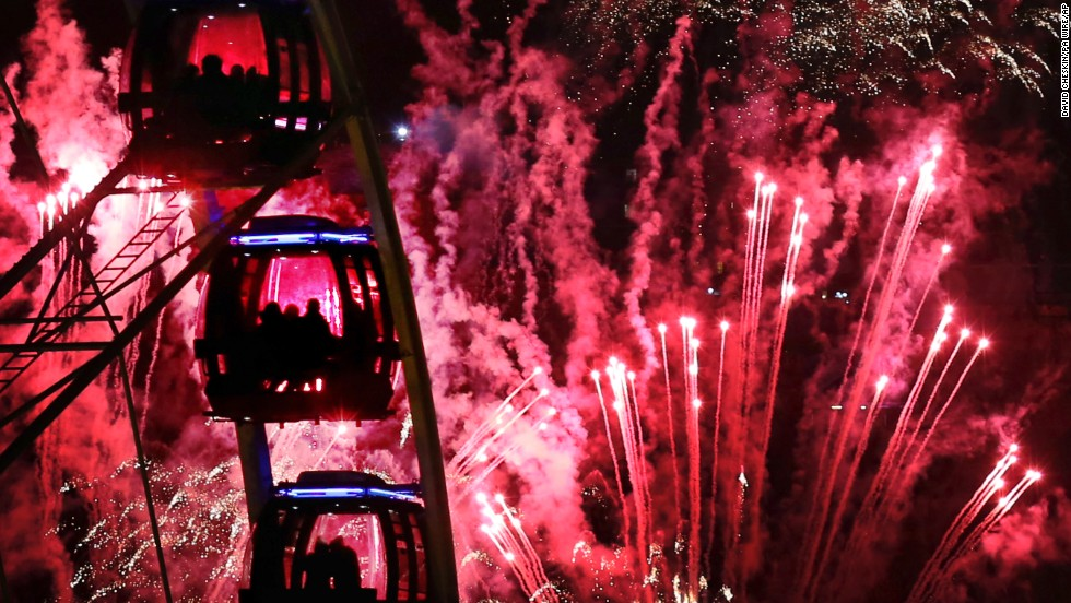 People ride a Ferris wheel as fireworks illuminate the sky during New Year's celebrations in Edinburgh, Scotland.