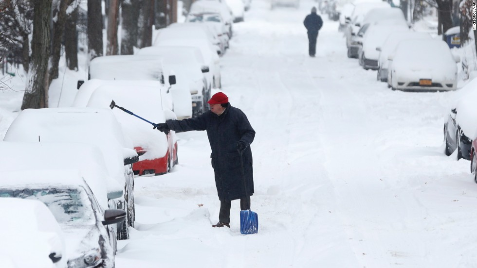 A man clears snow from a vehicle January 3 in Albany, New York.