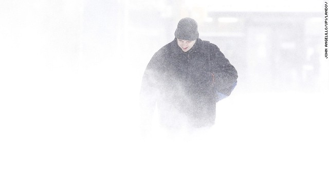 A man looks down while walking as the wind kicks up snow in blizzard like conditions in New York City on January 3, 2014.
