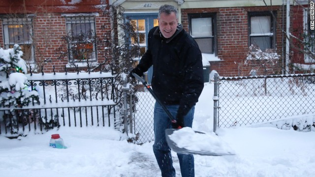 New York City Mayor Bill de Blasio shovels the sidewalk in front of his house in New York on Friday.