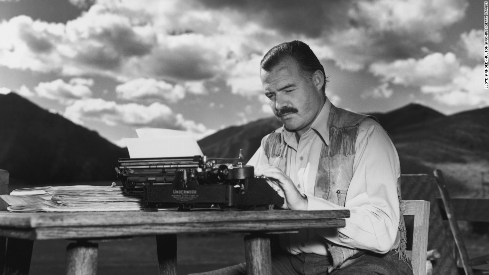 "Ernest Hemingway, who wrote ""For Whom the Bell Tolls"" and ""The Old Man and the Sea,"" works at his typewriter while sitting outdoors in 1939."