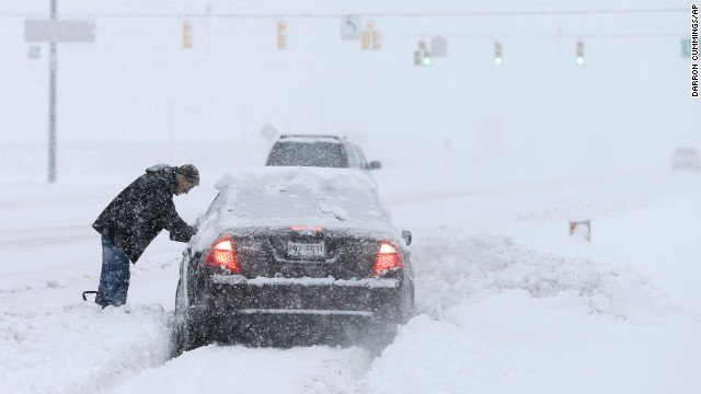 A motorist helps dig out a driver stuck in a snow drift Sunday, Jan. 5, 2014, in Zionsville, Ind. Snow that began in parts of Indiana Saturday night picked up intensity after dawn Sunday with several inches of snow on the ground by midmorning and more on the way.