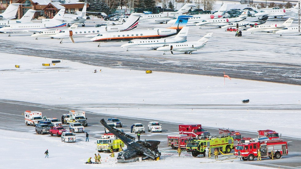 Firetrucks and ambulances surround the crash site. The airport tarmac is often filled with private planes owned or chartered by people who own vacation homes in the mountain resort community.