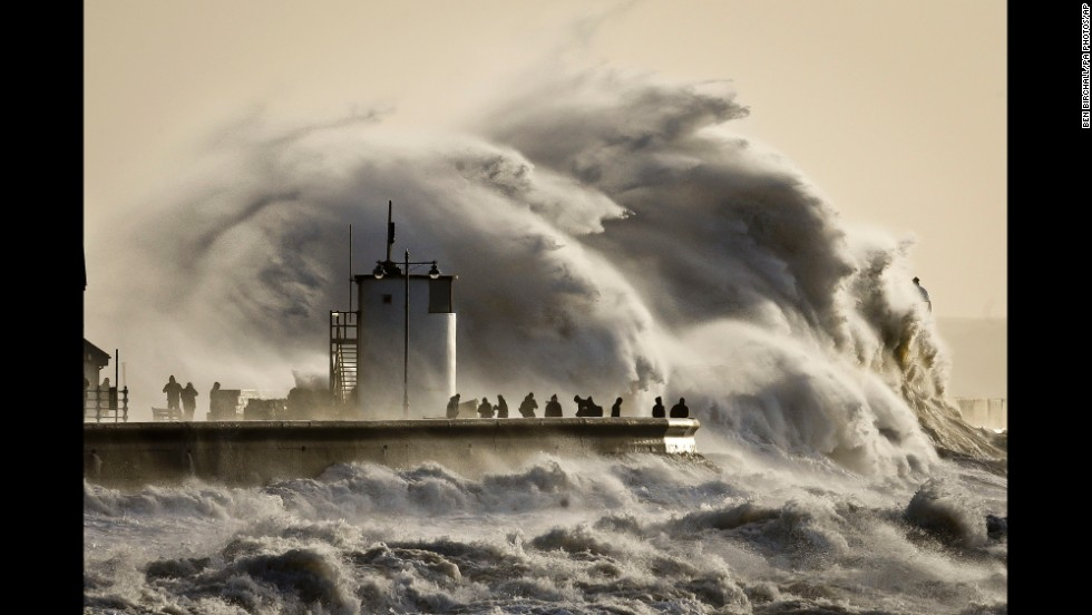 People watch enormous waves break in Porthcawl harbor in South Wales, United Kingdom, on January 6.