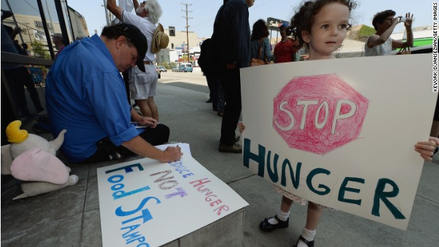 LOS ANGELES, CA - JUNE 17: Gracie Shannon-Sanborn, 5, holds a sign as she joins her father Allen Sanborn (L) and members of Progressive Democrats of America and other activists as they hold a rally in front of Rep. Henry Waxman's office on June 17, 2013 in Los Angeles, California. The protestors were asking the congressman to vote against a House farm bill that would reduce federal spending on the Supplemental Nutritional Assistance Program by $20.5 billion and affect food stamps and other services for the poor. (Photo by Kevork Djansezian/Getty Images)