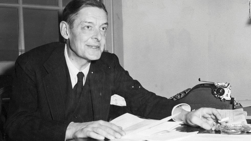 Poet T. S. Eliot inspects manuscripts in this undated photo.