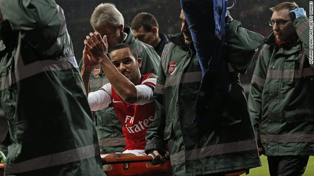 Arsenal's English midfielder Theo Walcott applauds as he leaves the pitch on a stretcher during the English FA cup third round football match between Arsenal and Tottenham Hotspur at the Emirates Stadium in London on January 4, 2014. Arsenal won the game 2-0. AFP PHOTO/ADRIAN DENNIS