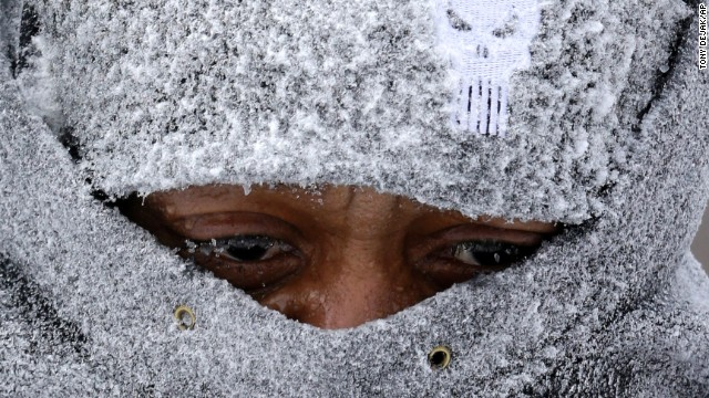 Hank Wade is bundled up as he clears snow from a sidewalk in Lyndhurst, Ohio, on Monday, January 6.