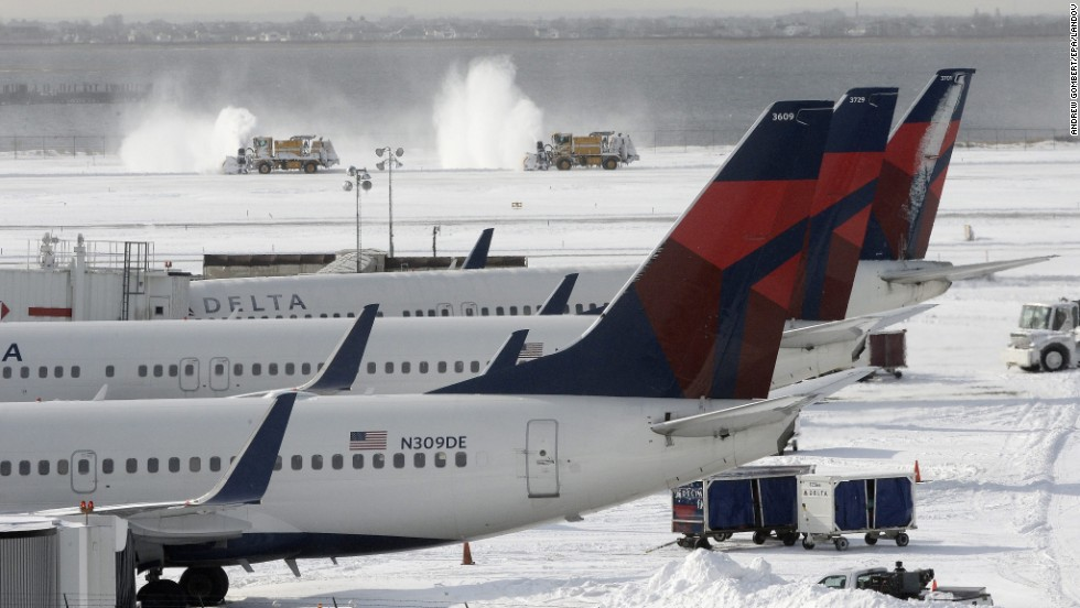 Snowplows clear snow from one of the runways January 3 at John F. Kennedy International Airport in New York City.