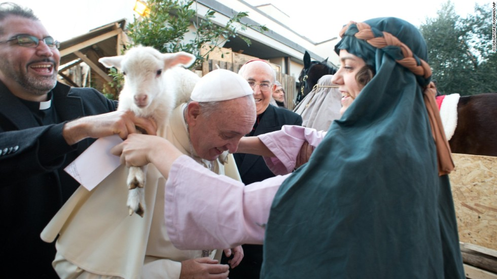 One of the nativity scene's participants places the lamb around the Pope's neck.