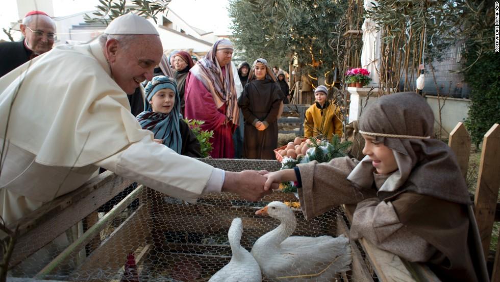 The Pope shakes hands with a boy.
