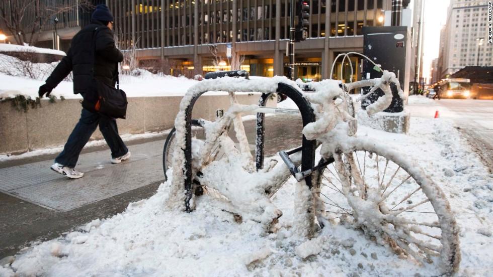 A man walks past a snow-covered bicycle in Chicago on January 7.