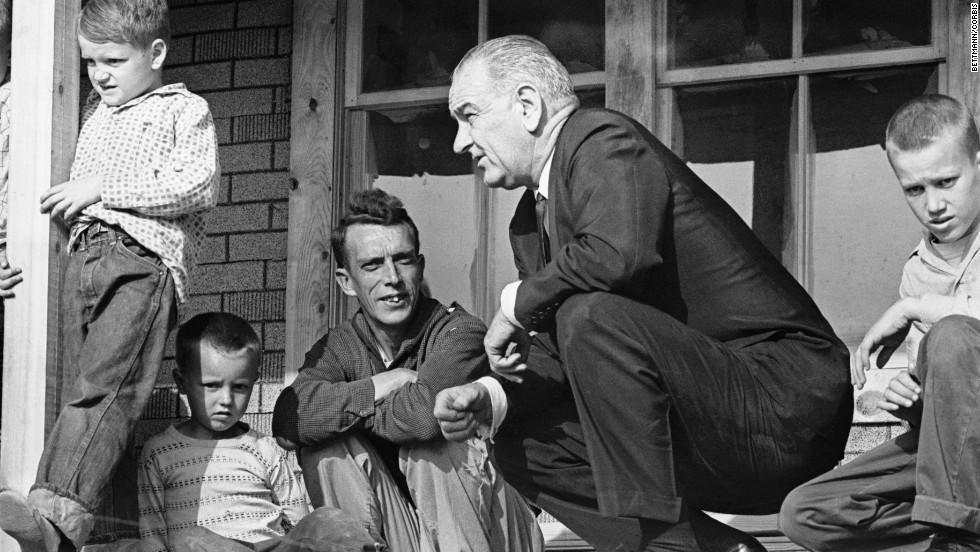 "U.S. President Lyndon B. Johnson visits a family in Inez, Kentucky, during a tour of poverty-stricken areas of the country in April 1964. Earlier that year, Johnson declared a ""war on poverty"" in his State of the Union address. He then worked with Congress to pass more than 200 pieces of legislation, which included early education programs and social safety nets such as Medicare and Medicaid."