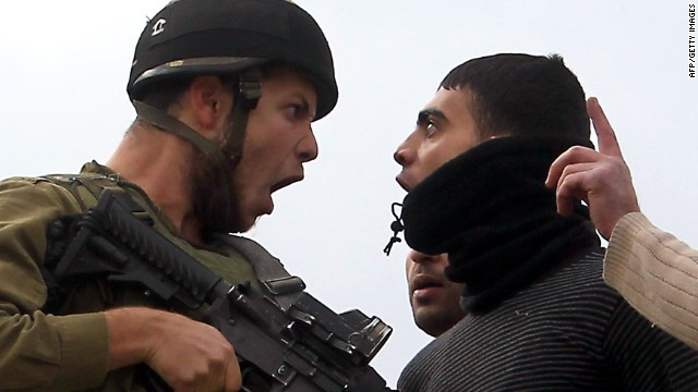 A Palestinian resident of the northern West Bank village of Madama argues with an Israeli soldier on December 17, 2012.