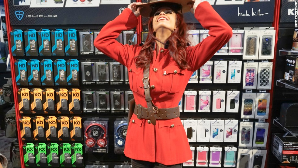 A promotion model dressed as a Canadian Mounted Police officer adjusts her hat for a portrait at the Gentec International Your Gateway to Canada booth.