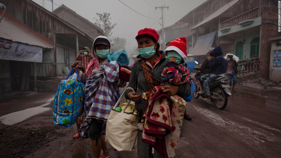 Women evacuate with their children to a temporary evacuation center on January 8 after their village is hit by ash.