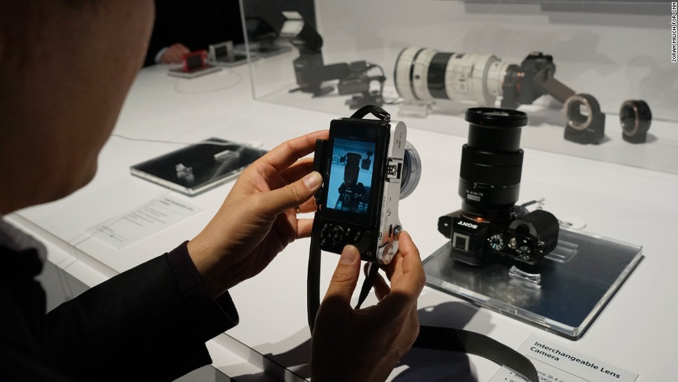 A person photographs the new 36.3-megapixel full-frame Sony Alpha 7R digital camera and a Vario-Tessar 24-70mm lens. The camera body costs $2,298, and the lens is $1,200.