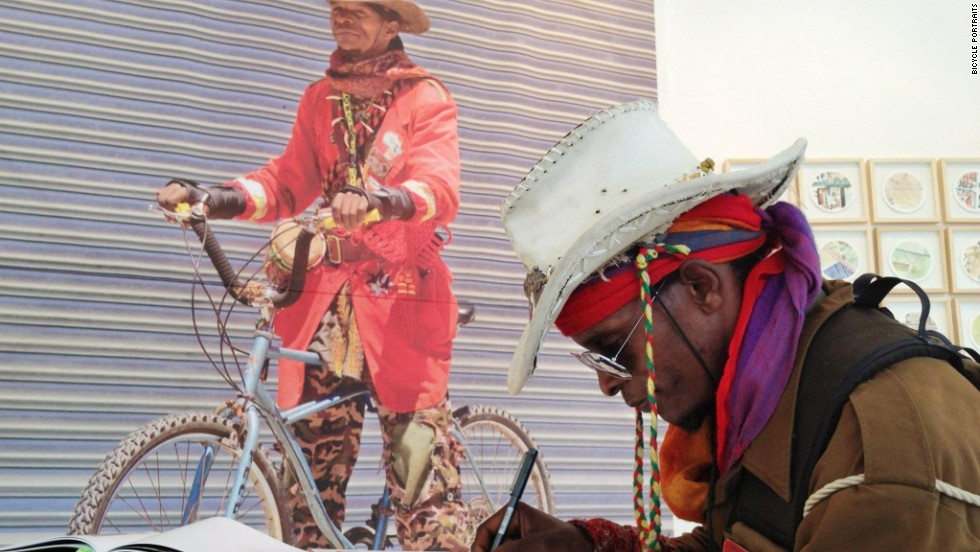 """Asher Tafara signing the """"Bicycle Portraits"""" book he appears in."""