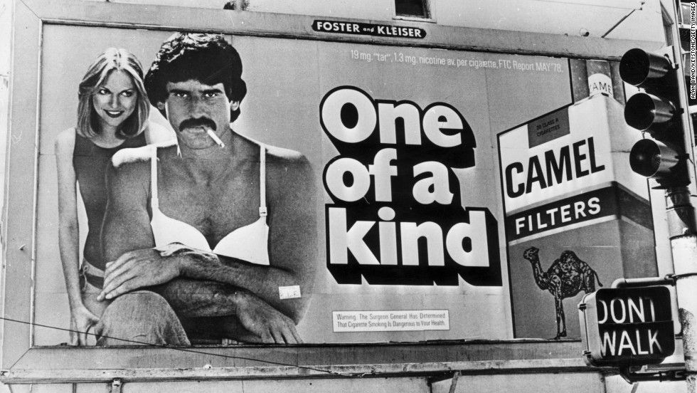A giant bra was added to this Camel ad in San Francisco by Billboard Liberation Front members who objected to the use of male bodies in ads. At the bottom of the billboard is the surgeon general's warning, which  were added to cigarette ads soon after Terry's report in 1964.