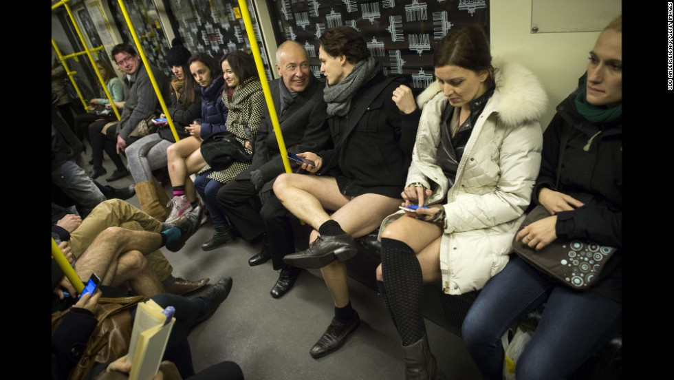 A man in his underwear shares a laugh with a fully clothed man on a train in Berlin.