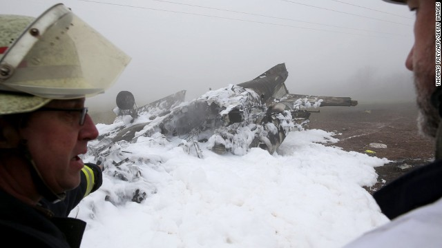 Fire workers stand in front of a burnt-out wreckage of a twin-engine business jet near Rivenich, Germany, on January 12.