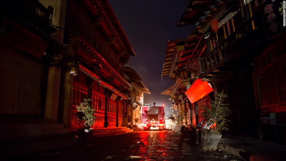 A fire truck navigates a narrow street.