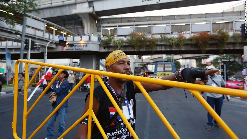 An anti-government protester moves a barricade across a major intersection in central Bangkok as part of their efforts to force the resignation of Thai Prime Minister Yingluck Shinawatra.