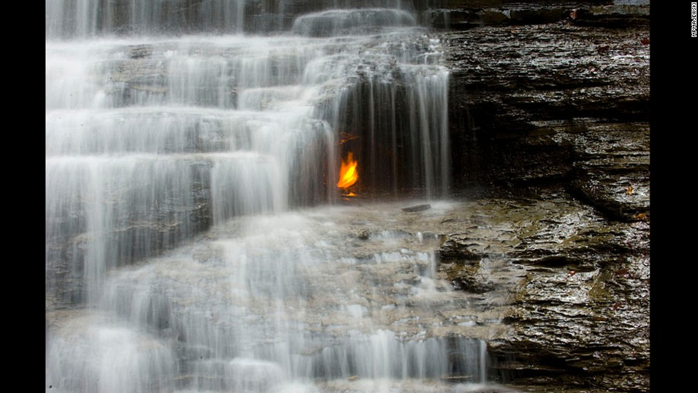 A golden flame flickers behind a small waterfall in the Shale Creek Preserve section of Chestnut Ridge Park. A geological fault allows methane gas to escape to the surface, where at some point a visitor set it alight.