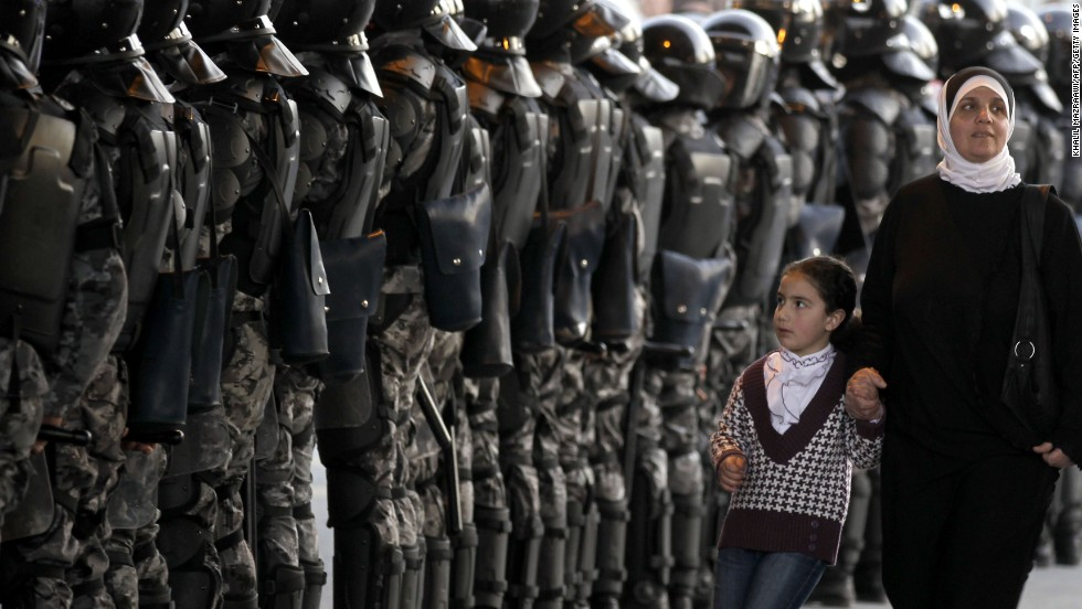 A woman and her daughter walk past Jordanian riot police standing guard at Jamal Abdual Nasser sqaure, in Amman, during demonstrations calling for political reforms in March 2012.