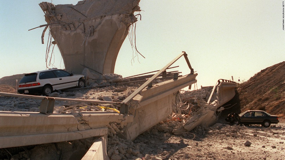A few hours after the earthquake, cars sit in the rubble of a collapsed highway ramp in Sylmar, California.
