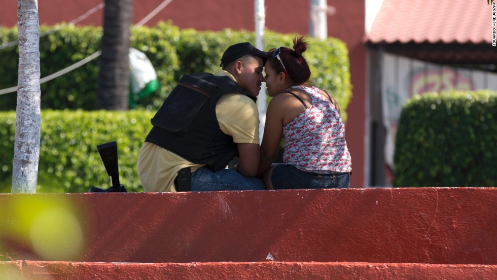 A man belonging to a group called the Self-Defense Council of Michoacan kisses a woman in Nueva Italia's main square on Monday, January 13.