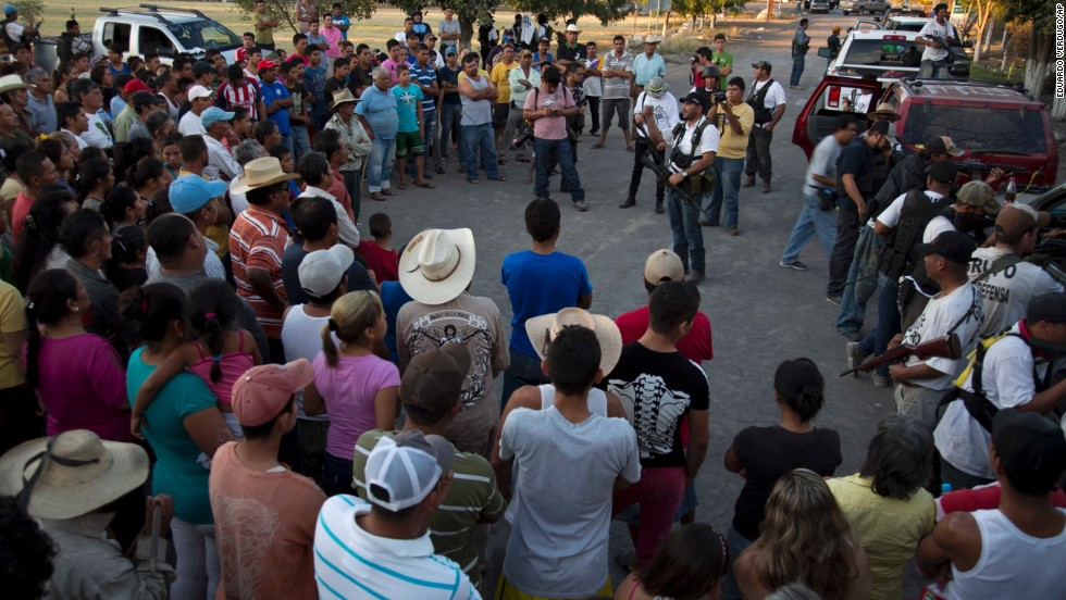 Members of a self-defense group talk to villagers after arriving in Las Yeguas in Michoacan state on Saturday, January 11. Some locals view the vigilantes as heroes, while others see them as villains.