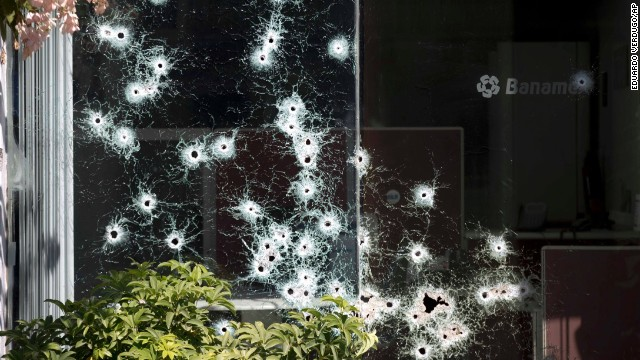 "The window of a bank is riddled with bullet holes in the town of Apatzingan, Michoacan state, Mexico, Saturday, Jan. 11, 2014. Residents from various towns in western Michoacan are protesting the arrival of vigilantes, or members of ""self-defense"" groups, to their communities by destroying property. Vigilante groups have formed to confront drug cartels in parts of Michoacan. (AP Photo/Eduardo Verdugo)"