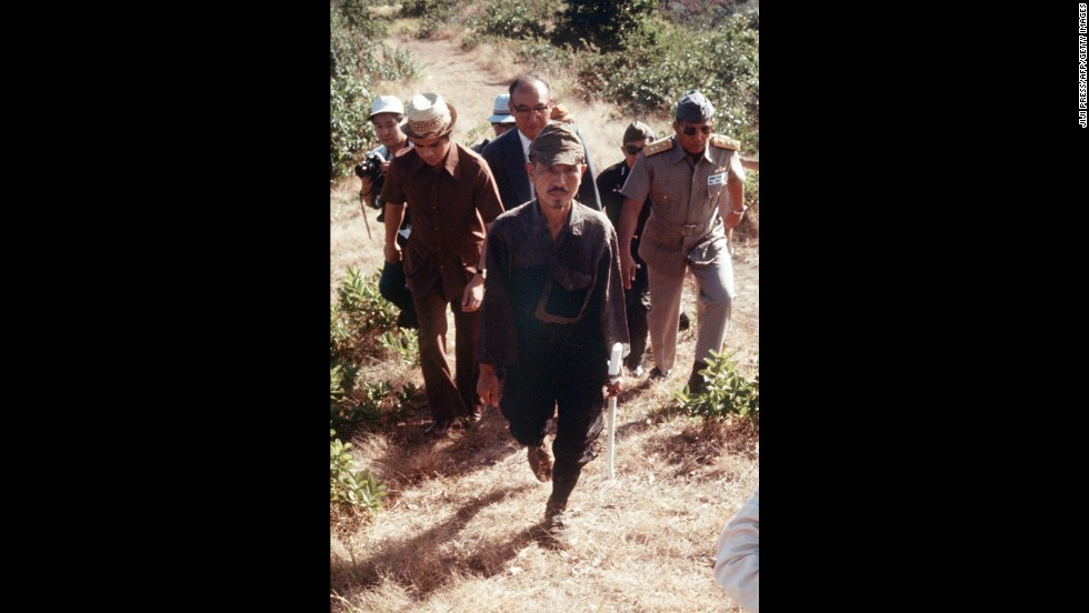 In March 1974, Onoda, center, walks from the jungle where he had survived since World War II on Lubang Island.