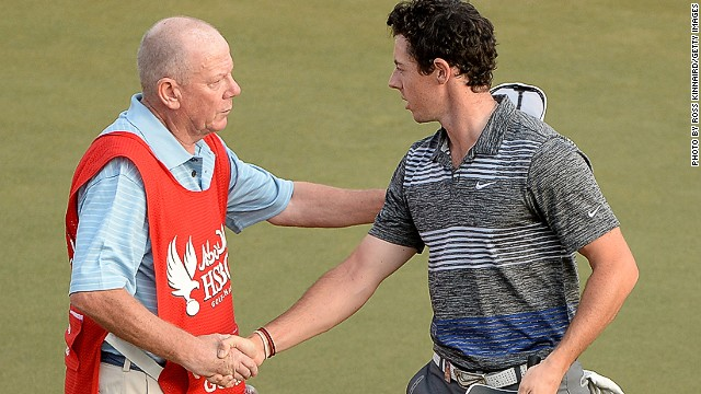 Caddie Dave Renwick (left) is the bearer of bad news for Rory McIlroy on the 18th green in Abu Dhabi