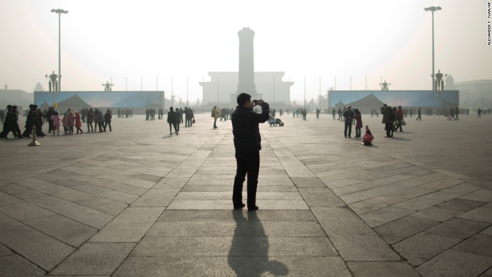 A tourist takes photos during a heavily polluted day in the capital's Tiananmen Square on January 16.