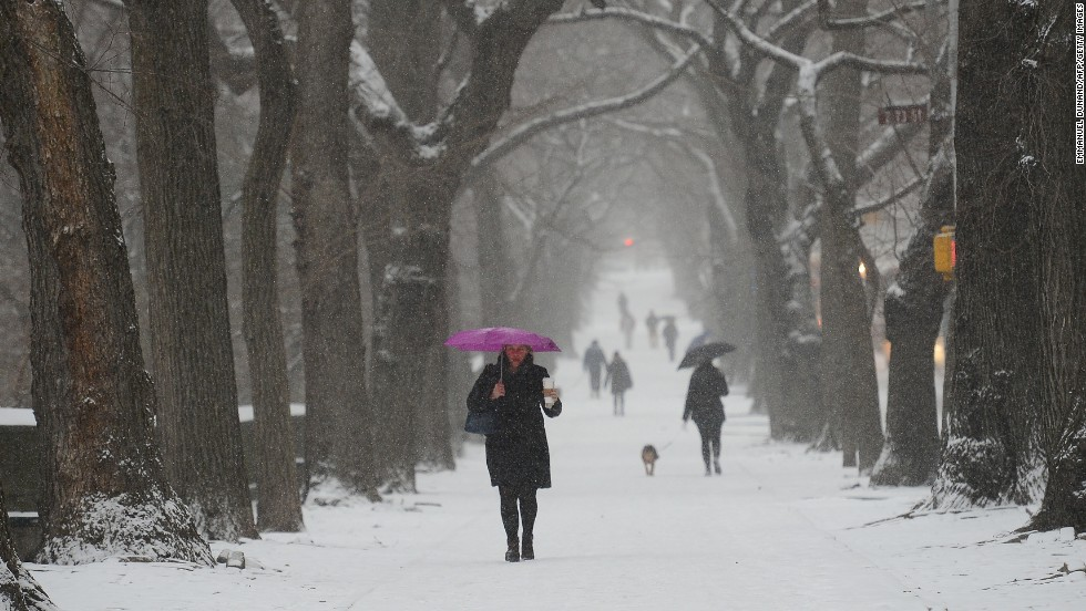 People walk with umbrellas through snow fall in New York on January 21.