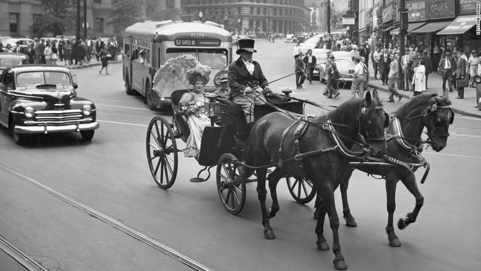 A carriage driver in a top hat and a passenger in a mutton-sleeved dress, shielding herself with a fancy umbrella, splendidly conjure up the past on a 1947 New York City street.