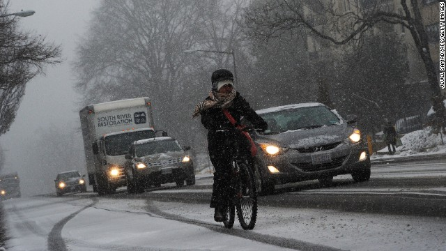 Commuters make their way under a snowfall on January 21, 2014 in Washington, DC.