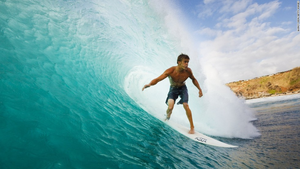 """A surfer rides a perfect wave at Honolua Bay, on Maui. Locals may respond to requests for directions with """"go back home,"""" but this is a world-class ride with the added bonus of whale spotting from your board."""