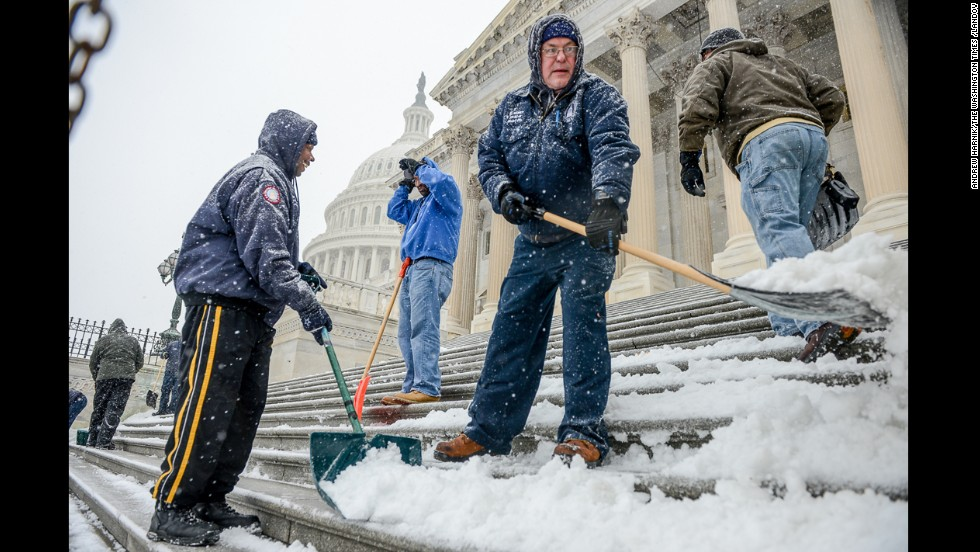 Workers clear snow off the steps of the U.S. Capitol in Washington on January 21.