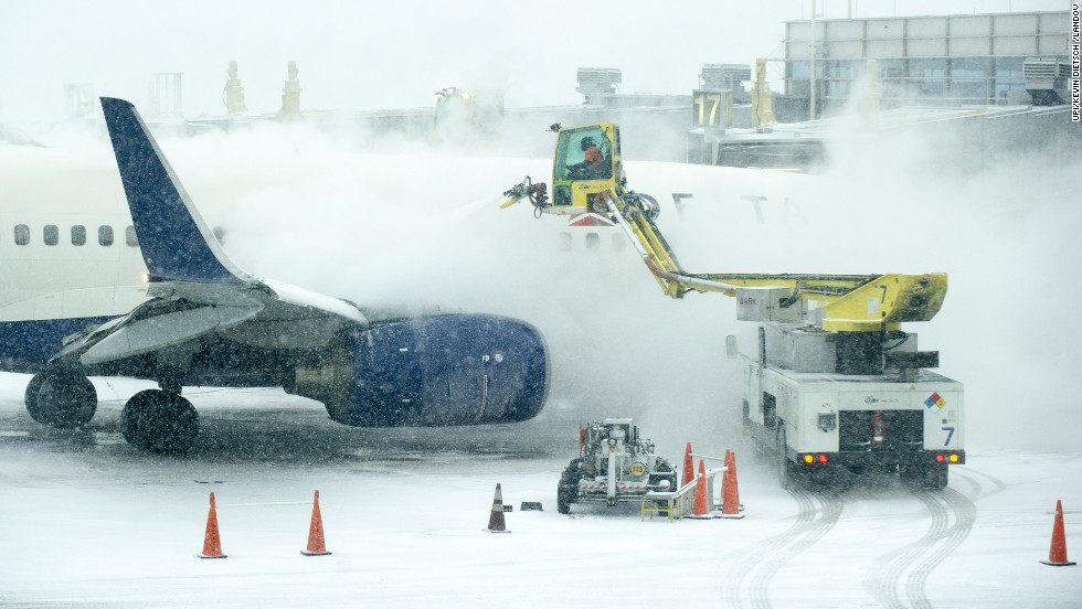 An airplane is de-iced as heavy snow falls at Ronald Reagan National Airport in Arlington, Virginia, on January 21.